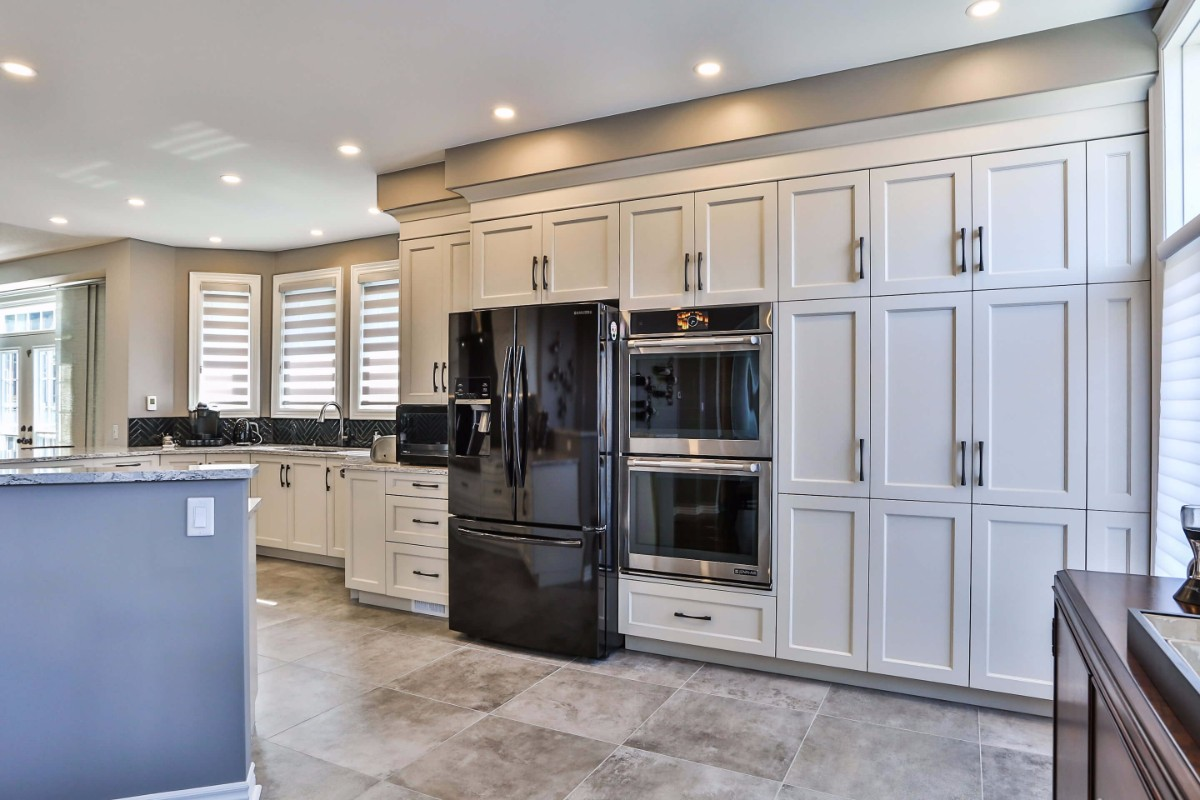 White kitchen design with a double oven, white cupboards and beautiful, custom window coverings.