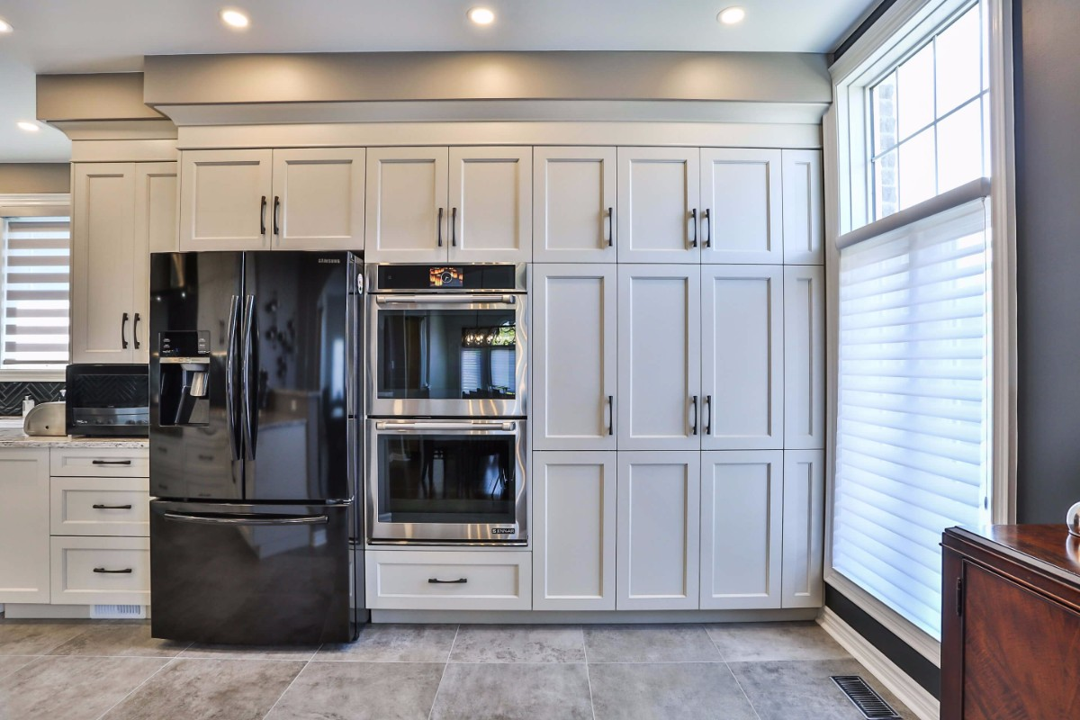 White kitchen design with custom window treatments, tile flooring and updated appliances.