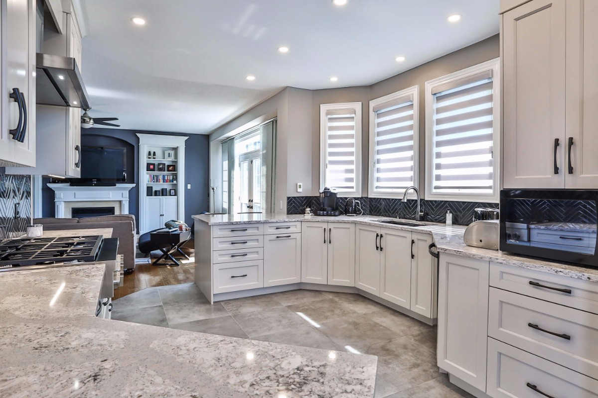 White kitchen design with generous counter space, custom window treatments and white cupboards.