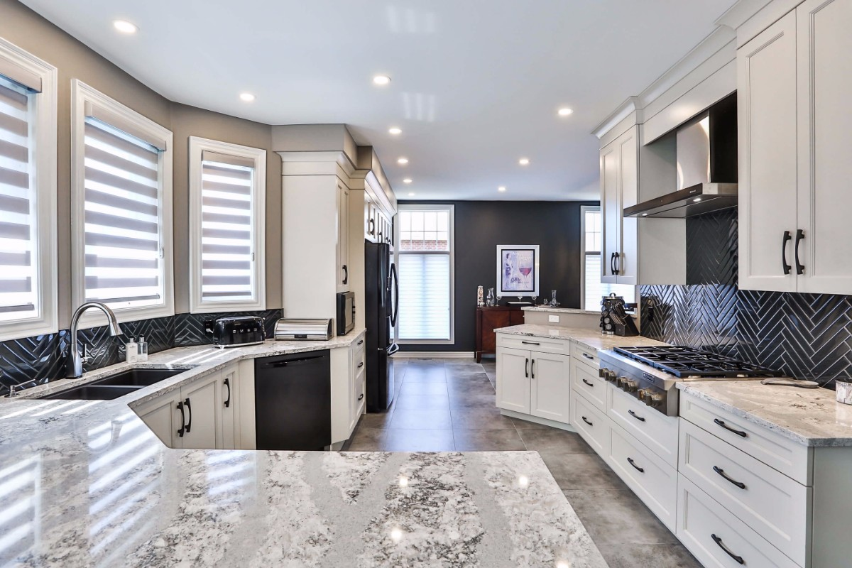White kitchen design with generous counter space and a dark tile backsplash.