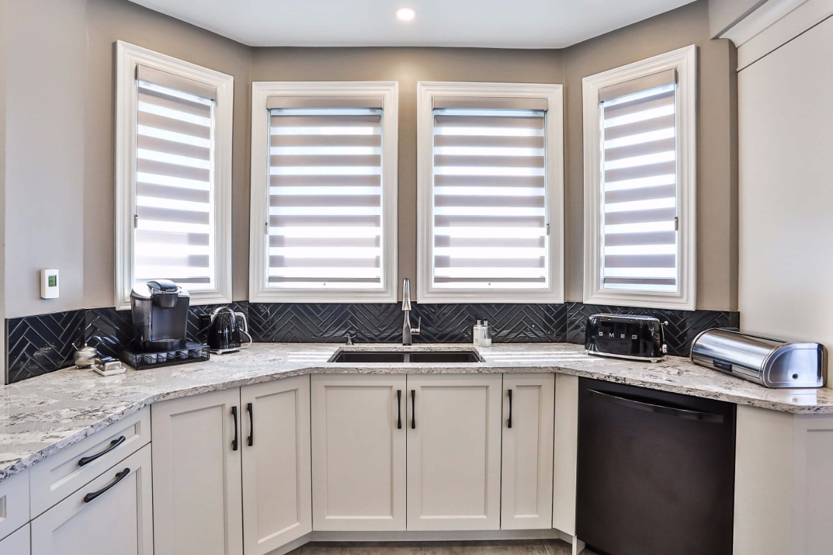 White kitchen design with white cupboards and contemporary finishings.