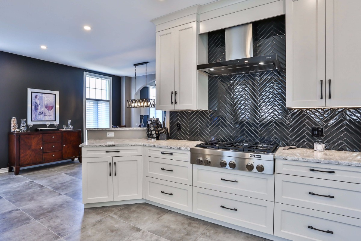 White kitchen design with white cupboards, a dark tile backsplash and tile floors.