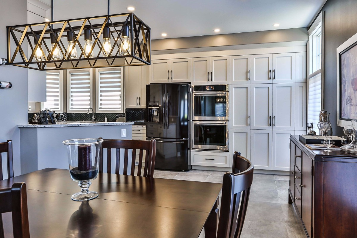 White kitchen design with white cupboards, pot lights, chic light fixtures and ample storage space.