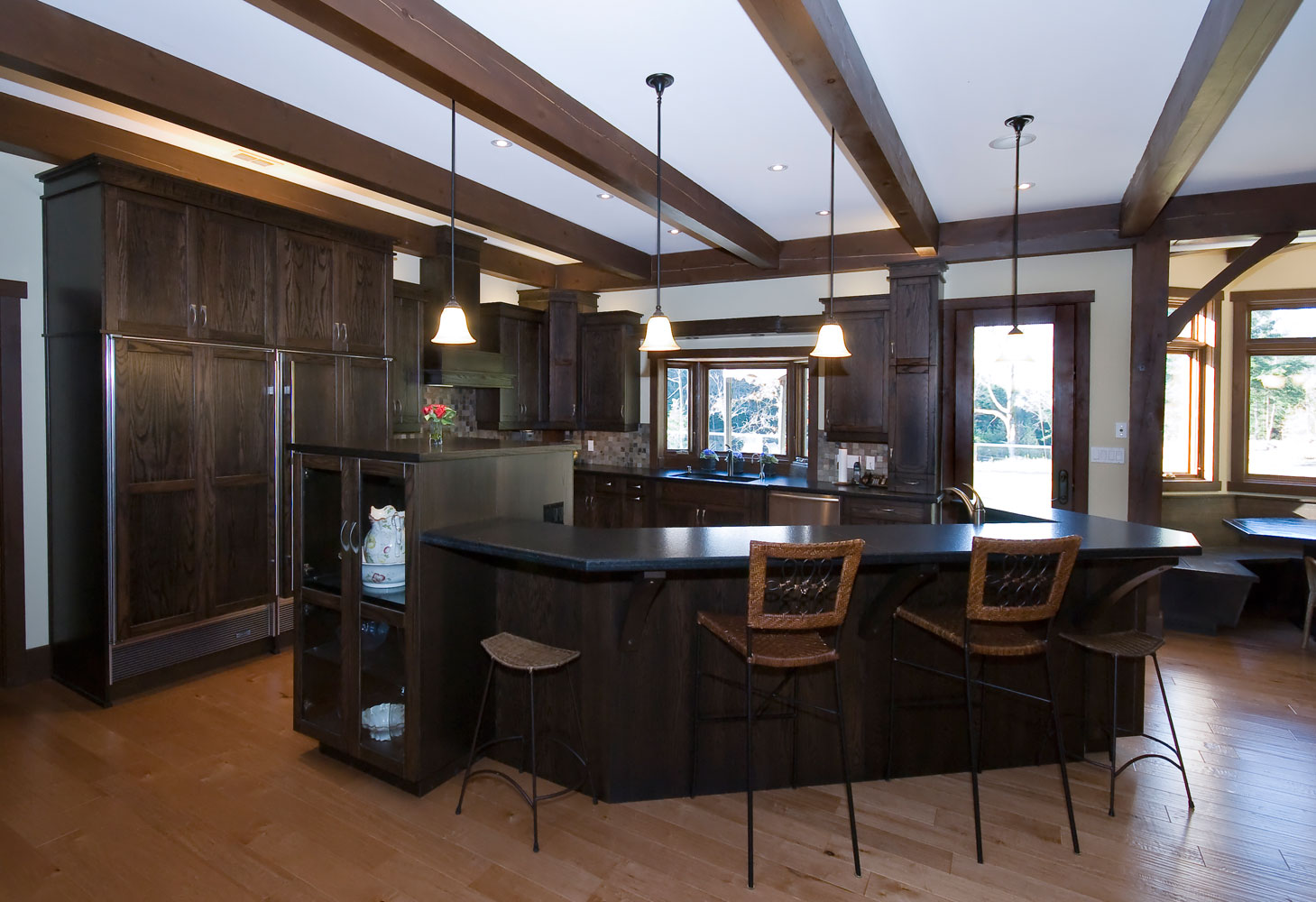 large kitchen design with dark wood cabinets, hardwood floors, stainless steel appliances, and wood ceiling beams - Total Living Concepts barrie ontario