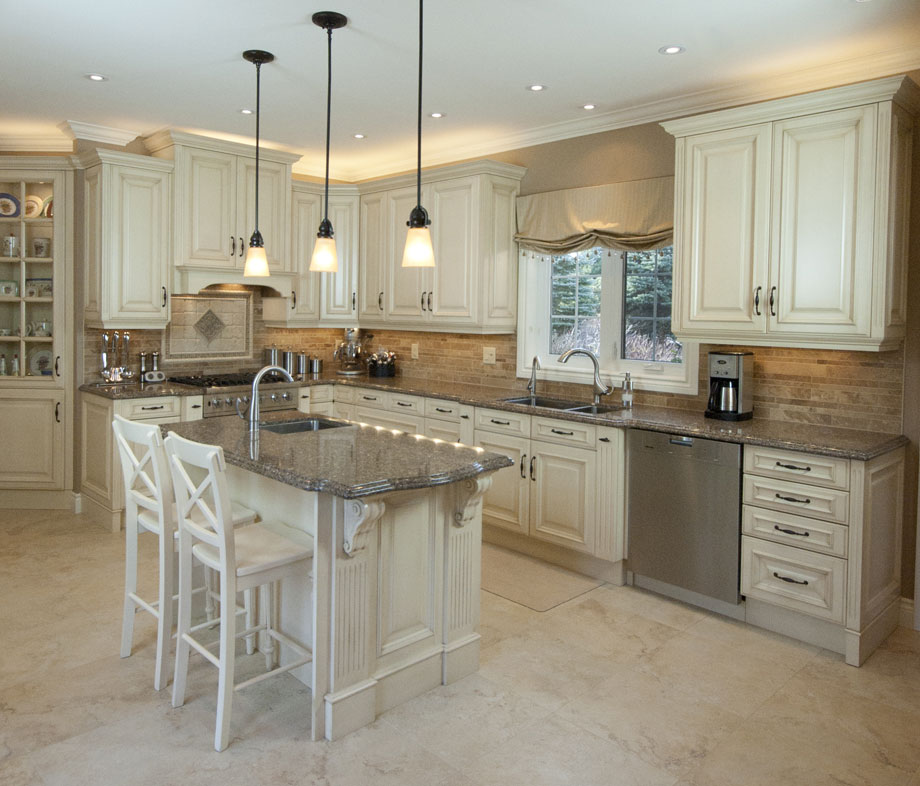 Large traditional kitchen design and renovation featuring cream colored cabinets, large island, granite countertops, a hidden fridge, tile floors, and convenient hidden drawers and cabinets providing plenty of storage - Total Living Concepts barrie ontario