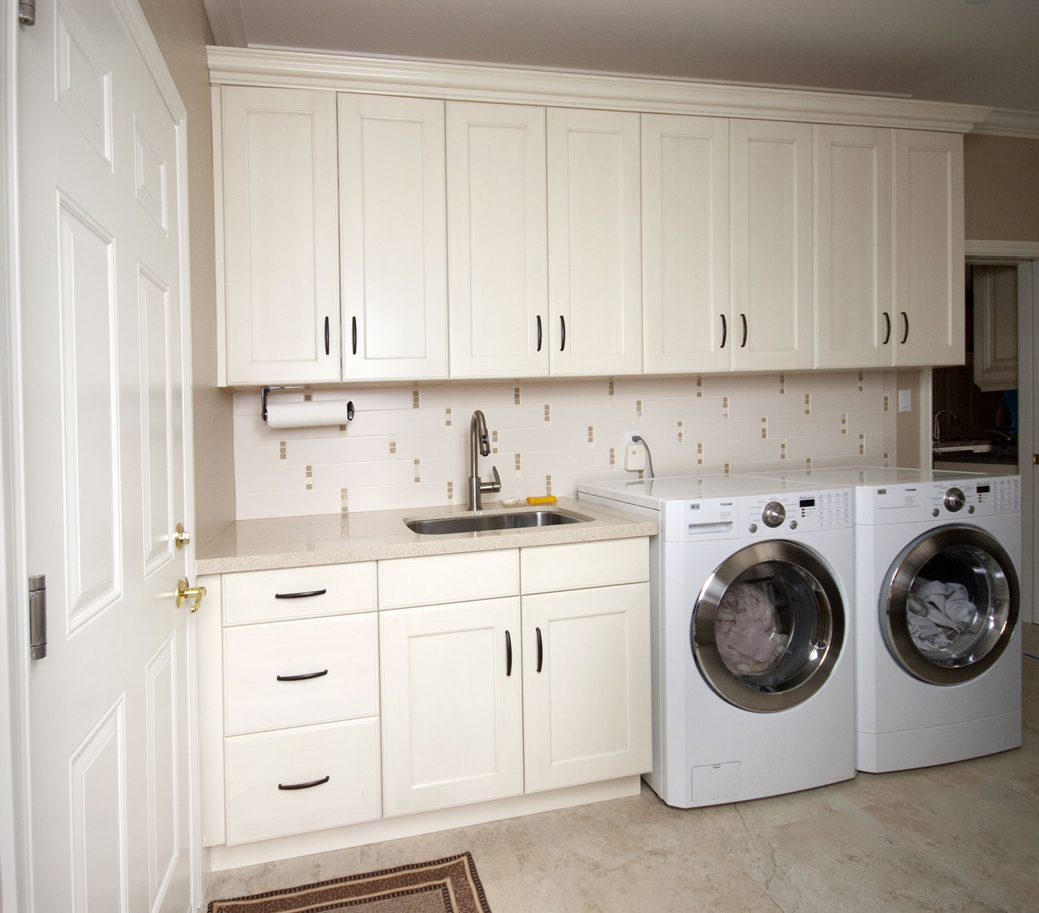 Laundry Room Renovation with cream colored cabinets and white appliances