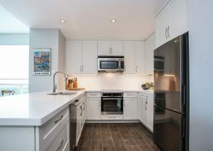 Small white kitchen design and renovation featuring white cabinets and stainless steel cabinets