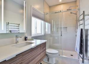 White bathroom design with tile flooring, large stand up shower with rain shower head, stainless steel accents including warming towel rack, and gleaming white vanity with sunken sink and teak cabinets