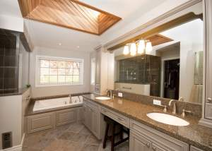 Large traditional ensuite design and renovation with dual sinks, makeup desk, large tub and separate walkin shower, skylight - Total Living Concepts barrie ontario
