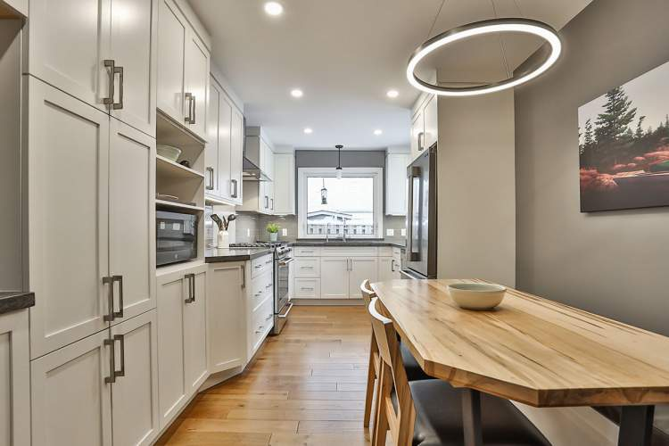 Galley kitchen renovation featuring white kitchen cabinets with tons of storage, stainless steel appliances, warm grey accents, and natural wood flooring.