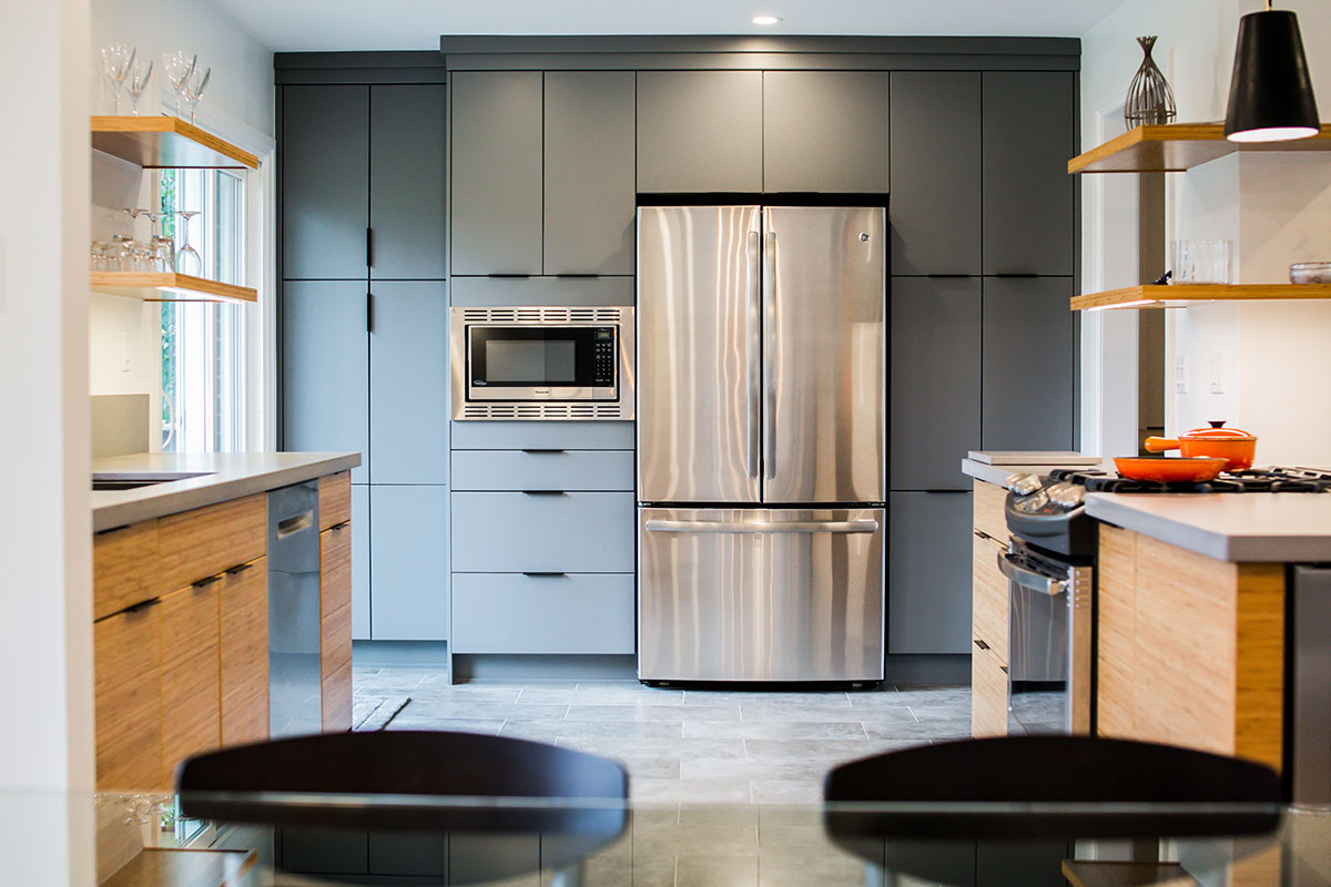 Kitchen design featuring 2-tone greyish blue and wood cabinets with stainless steel appliances