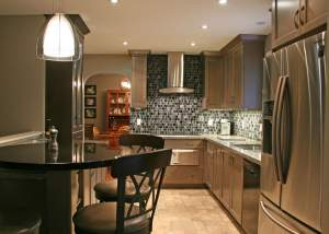 Modern kitchen design with warm grey cabinets, stainless steel appliances, tile flooring, and round bar table - Total Living Concepts barrie ontario
