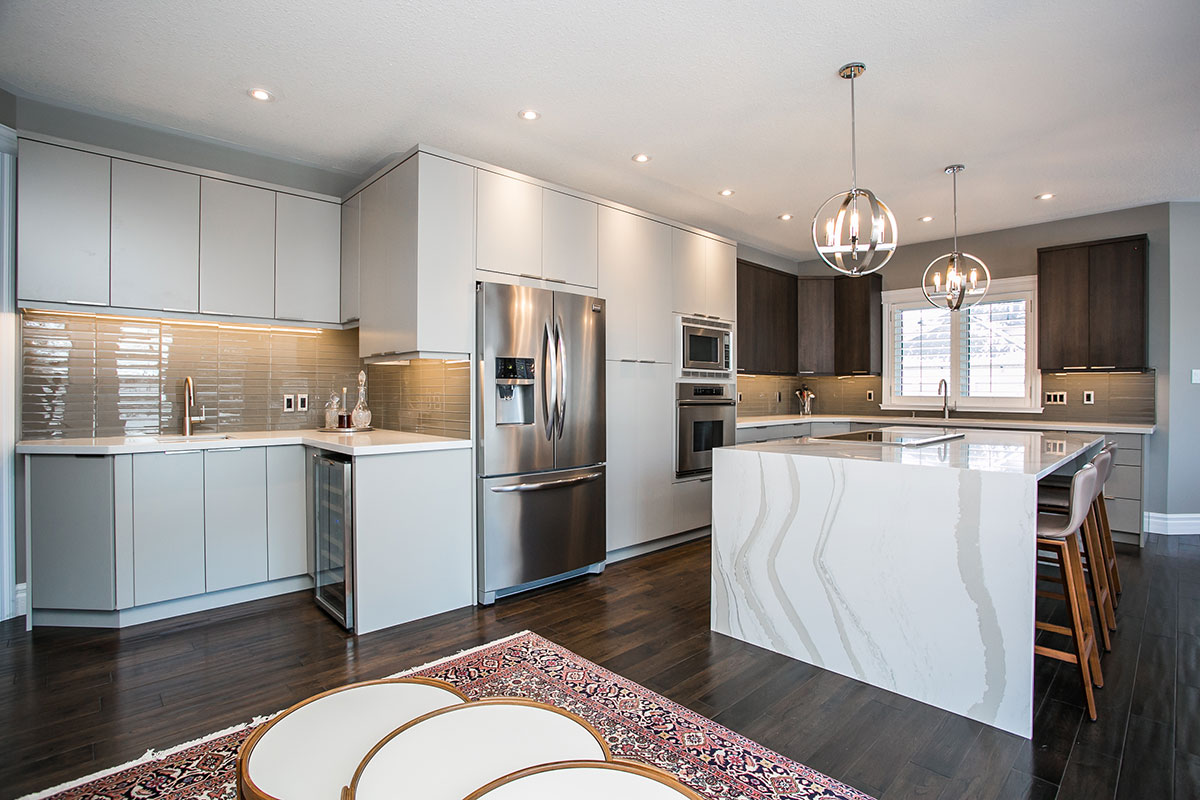 Modern transitional kitchen design featuring 2-toned cabinets and light grey and dark walnut, wine bar, large island, and stainless steel appliances with wall mounted microwave and oven