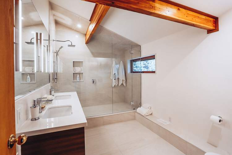 Clean modern bathroom design and renovation project featuring exposed wood beams highlighting a vaulted ceiling, double sinks, and a large walkin shower with two shower heads and a window to view the beautiful outdoors.