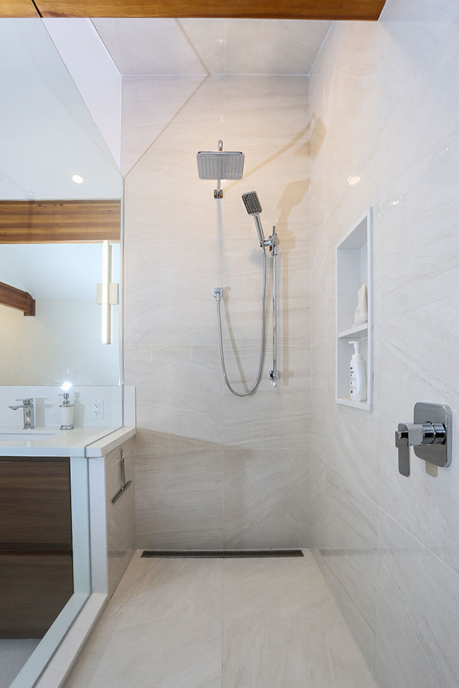 Ensuite featuring large walkin shower with two stainless steel shower heads and recessed cubby holes